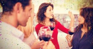 Image composée des amis ayant le vin tout en se tenant ensemble Images stock