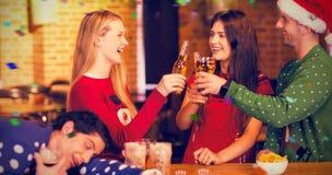Image composée des amis de sourire ayant des boissons pendant le Noël Photographie stock libre de droits