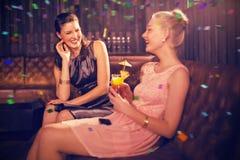 Image composée des amis féminins agissant l'un sur l'autre les uns avec les autres tout en ayant le cocktail Image stock