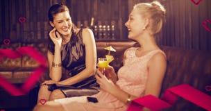 Image composée des amis féminins agissant l'un sur l'autre les uns avec les autres tout en ayant le cocktail Photos stock