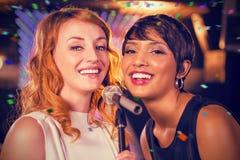 Image composée des amis féminins chantant ensemble dans la barre Photo stock