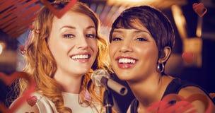 Image composée des amis féminins chantant ensemble dans la barre Photographie stock