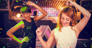 Image composée des amis féminins de sourire dansant sur la piste de danse Images libres de droits