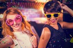 Image composée des amis féminins de sourire dansant sur la piste de danse Photos libres de droits