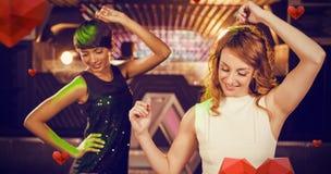 Image composée des amis féminins de sourire dansant sur la piste de danse Photos stock