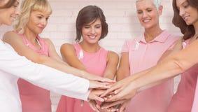 Image composée des amis féminins empilant des mains pour la conscience de cancer du sein Image stock