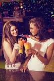 Image composée des amis féminins grillant des verres de cocktail au compteur de barre Photographie stock libre de droits