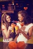 Image composée des amis féminins grillant des verres de cocktail au compteur de barre Photos libres de droits