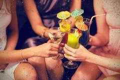 Image composée des amis féminins grillant des verres de cocktail dans la barre Photographie stock libre de droits