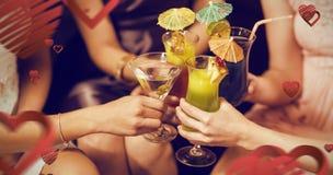Image composée des amis féminins grillant des verres de cocktail dans la barre Image stock