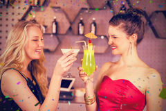 Image composée des amis féminins grillant un verre de cocktail dans la barre Photos libres de droits