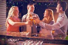 Image composée des amis grillant des verres de bière au compteur de barre Images libres de droits