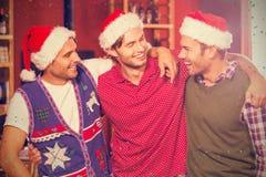 Image composée des amis heureux avec des chapeaux de Noël Photos stock