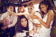 Image composée des amis heureux buvant du champagne Images libres de droits