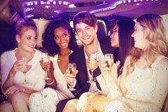 Image composée des amis heureux buvant du champagne tout en se reposant Photos libres de droits