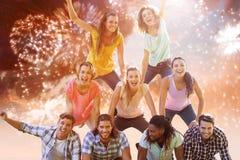 Image composée des amis heureux en parc faisant la pyramide humaine Image libre de droits