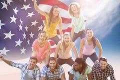 Image composée des amis heureux en parc faisant la pyramide humaine Photos stock