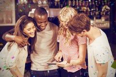 Image composée des amis heureux regardant le smartphone Photo stock