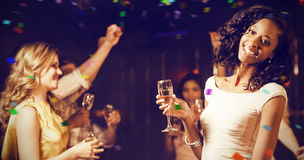 Image composée des amis heureux tenant la cannelure de champagne tout en dansant Images stock