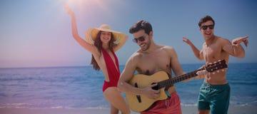 Image composée des amis jouant la musique dans les vêtements de bain Image stock
