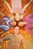 Image composée des amis se situant en cercle et souriant à l'appareil-photo Images libres de droits