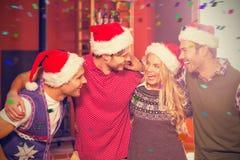 Image composée des amis utilisant des chapeaux de Noël regardant l'un l'autre Photo libre de droits