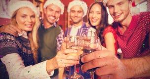 Image composée des amis utilisant des chapeaux de Noël tout en grillant Photo libre de droits