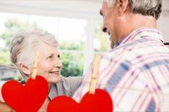 Image composée des coeurs accrochants rouges et des couples supérieurs dansant à la maison Image stock