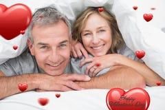 Image composée des couples affectueux sous la couette Images stock