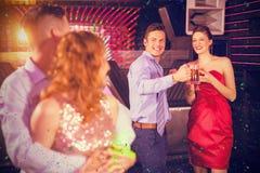 Image composée des couples agissant l'un sur l'autre avec des amis tout en dansant Images libres de droits