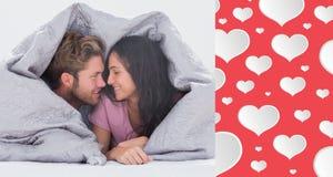 Image composée des couples attrayants enveloppés dans la couette Photos stock