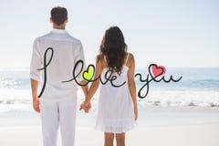 Image composée des couples attrayants tenant des mains et observant l'océan Images stock