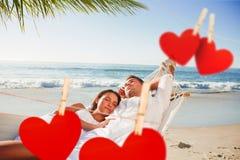 Image composée des couples calmes faisant une sieste dans un hamac Images stock