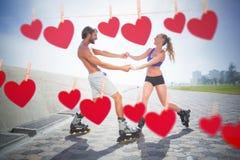 Image composée des couples d'ajustement faisant du roller ensemble sur la promenade Photographie stock