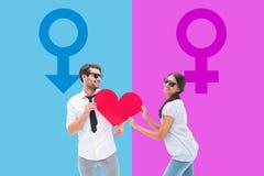 Image composée des couples de hippie souriant à l'appareil-photo tenant un coeur Image stock