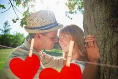 Image composée des couples de sourire mignons se penchant contre l'arbre en parc Images stock