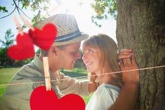 Image composée des couples de sourire mignons se penchant contre l'arbre en parc Photos stock