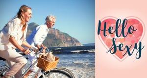 Image composée des couples de sourire montant leurs vélos sur la plage Photographie stock libre de droits