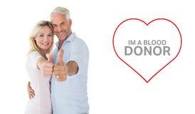 Image composée des couples de sourire montrant des pouces ensemble Images stock