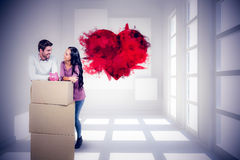 Image composée des couples de sourire tenant dessus des boîtes avec l'épargnant porcin Photos stock