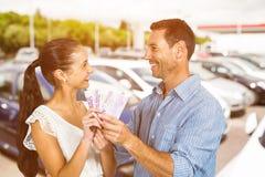 Image composée des couples de sourire tenant l'argent Photo libre de droits
