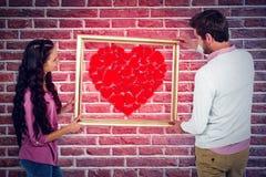 Image composée des couples de sourire tenant le cadre de tableau Photo libre de droits
