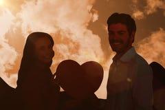 Image composée des couples de sourire tenant le coeur de papier Photo stock