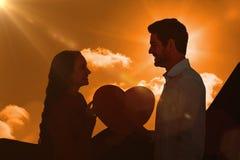 Image composée des couples de sourire tenant le coeur de papier Image stock