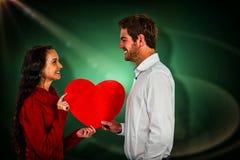 Image composée des couples de sourire tenant le coeur de papier Photos libres de droits