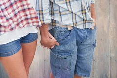 Image composée des couples en chemises et denim de contrôle tenant des mains Images stock