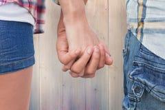 Image composée des couples en chemises et denim de contrôle tenant des mains Photographie stock libre de droits
