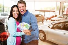 Image composée des couples enthousiastes tenant l'argent Photographie stock