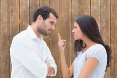 Image composée des couples fâchés faisant face pendant l'argument images stock