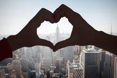 Image composée des couples faisant la forme de coeur avec des mains Photos stock